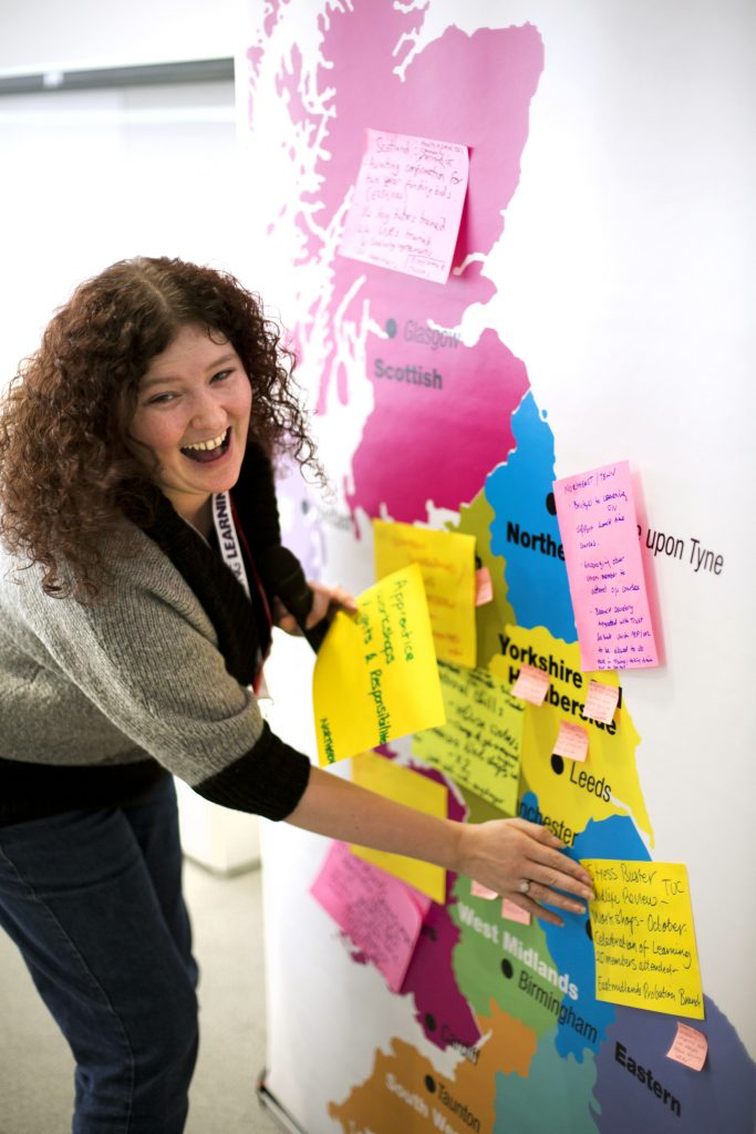 Woman sticking post-it notes to a large map of the United Kingdom